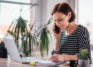 Mujer teletrabajando hablando por teléfono CHC Energía